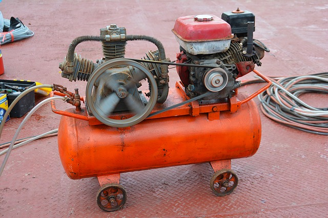 An orange air compressor sitting on a rust color industrial floor.