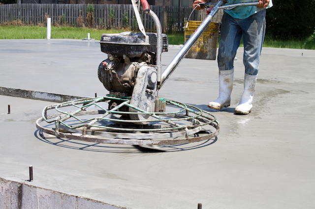 Construction worker uses a motorized power trowel, or concrete finisher, to smooth and finish a concrete slab.